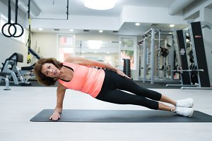 Beautiful fit senior woman working her abs, doing side plank.