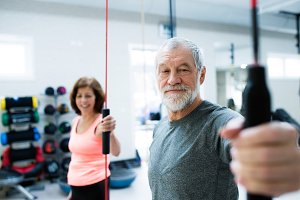 Senior couple in gym working out with vibration bars