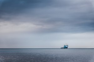 Ship on the horizon and dark clouds