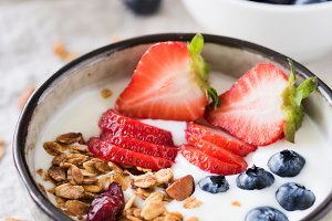 Yogurt with granola, strawberries and blueberries in bowl