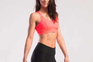 Fit woman in sports bra and shorts. Studio shot, gray background