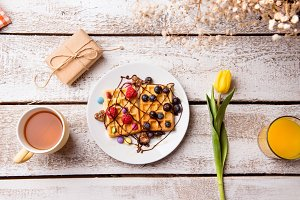 Breakfast meal, gift and flower. Studio shot, wooden background.