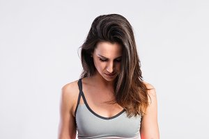 Attractive young fitness woman in gray tank top. Studio shot.