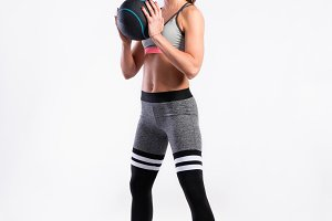 Fit woman in sports clothing holding medicine ball, studio shot