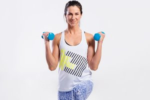 Young fit woman working out with dumbells. Studio shot.