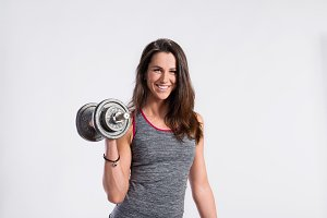 Fitness woman holding dumbell. Studio shot, gray background.