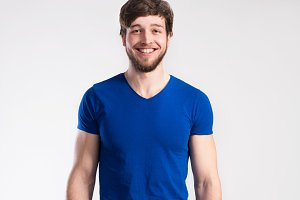 Handsome fitness man in blue t-shirt, studio shot.