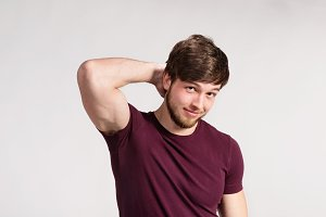 Handsome hipster fitness man in burgundy t-shirt, studio shot.