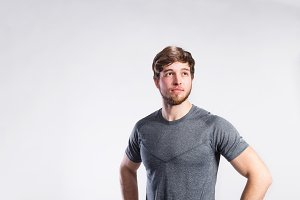 Handsome fitness man in gray t-shirt, studio shot.