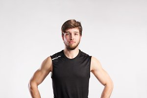 Handsome fitness man in black sleeveless shirt, studio shot.