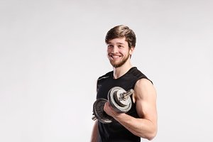 Handsome fitness man holding dumbbell, studio shot.
