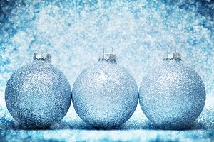 Christmas glass balls on cold frosty glitter background