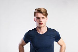 Young handsome hipster man in blue t-shirt, studio shot.