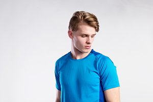 Young handsome hipster man in blue sports t-shirt, studio shot.
