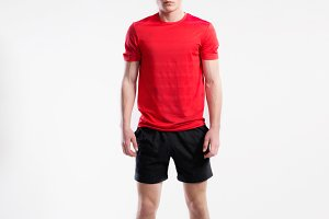 Handsome fitness man in red t-shirt and shorts, studio shot.