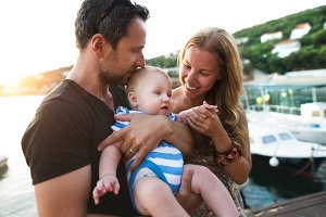 Parents with baby son enjoying their time at seaside.