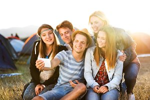 Teenagers at summer music festival, taking selfie with smartphon