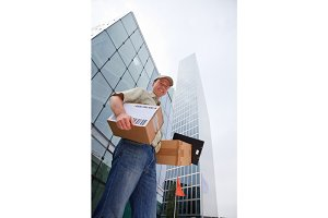 Delivery Boy Standing In Front Of Modern Buildings