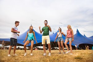 Teenagers at summer music festival dancing in front of tent