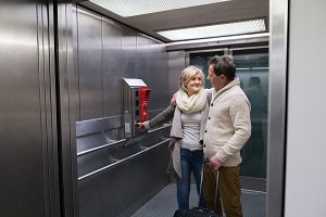 Beautiful senior couple with luggage standing in modern elevator