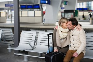 Senior couple waiting on train station, sitting on bench, kissin
