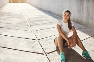Young lady runner sitting on a pavement getting ready for a long run looking at camera. Urban sport concept.