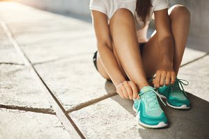 Sport is the way of life. Close-up of runner sneakers tying laces getting ready to run. Urban sport concept.