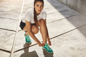Fit young woman tying her laces ready to start her morning jogging in an urban environment. Urban sport concept.