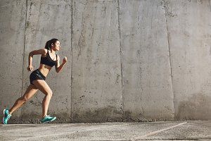 Strong woman running forward to success in her fitness life. Urban sport concept.