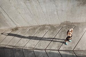 Wide shot of female runner stretching to take a jog into bright and sunny future. Urban sport concept.