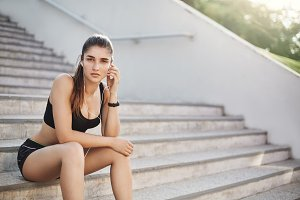 Young and confident female fitness trainer listening to upbeat music to start her everyday urban workout on a stairway to perfect body.