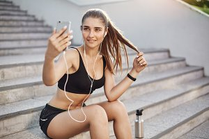 Female running traner taking a selfie with a smart phone listening to rock music in her white wired earphones. Making all of her girl friends pink with envy of her perfect body.
