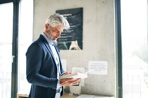 Mature businessman with a book in the office.