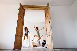 Young couple moving in a new house, jumping up high.