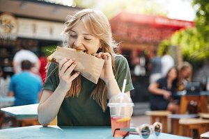 Girl eating taco. Hungry freckled blonde woman eating junk food on a food court on a sunny summer day in park.