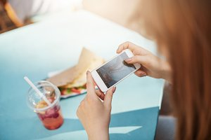 Food blogger making photos. Close up of a girl using a smartphone to capture her food and share on social media or mail to her friends.