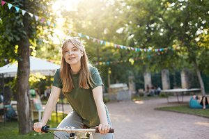 Blonde woman riding a bike. Portrait of young nordic girl riding a bycicle in a city park smiling on camera looking happy wearing green on a sunny summer day. Healthy lifestyle concept.