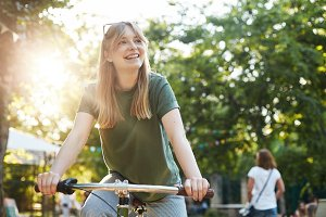 Portrait of young beautiful blonde woman enjoying pretending to ride a bicycle in the park during a food festival smiling off camera