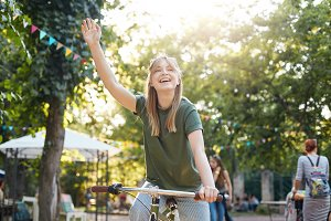 Girl riding bike in park. Portrait of a young female riding a bycicle outdoors in city park and waving her friends or boyfriend smiling. Healthy lifestyle concept.