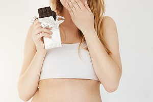 Pretty pregnant woman surprised that her chocolate bar is so tasty and worrying she will gain weight.