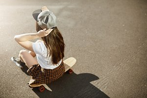 Female skateboarding champion sitting on her longboard wearing a hat on a sunny day in an urban environment.