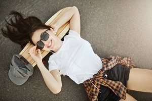 Female skateboarder laying on concrete and her longboard wearing shades looking at camera