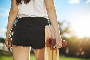 Close up of female skateboarder having fun in park holding her longboard.