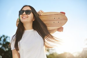 Young woman holding skateboard or longboard wearing sunglasses on a sunny summer day in park.