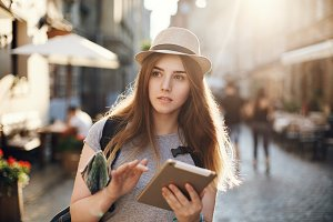 Female tourist lost in small european city looking for directions in her tablet, holding a map. Travel concept.