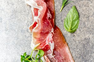 Food background with ham jamon serrano and herbs - rosemary, basil and watercress salad, stone gray background, top view