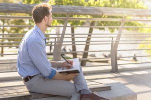 Businessman with notepad on bench