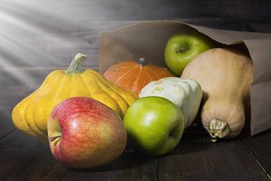 Autumn vegetables under the sun in the basement. Pumpkins, apples, squash, autumn leaves on a wooden table. Harvest.