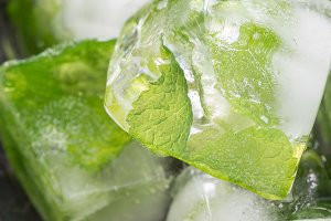 Homemade ice cubes with mint leaves inside on metal plate, ice for lemonade and cocktail, vertical, closeup