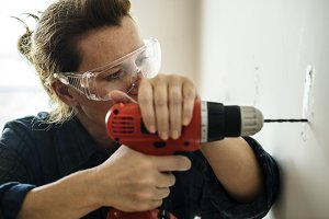 A carpenter using a drill